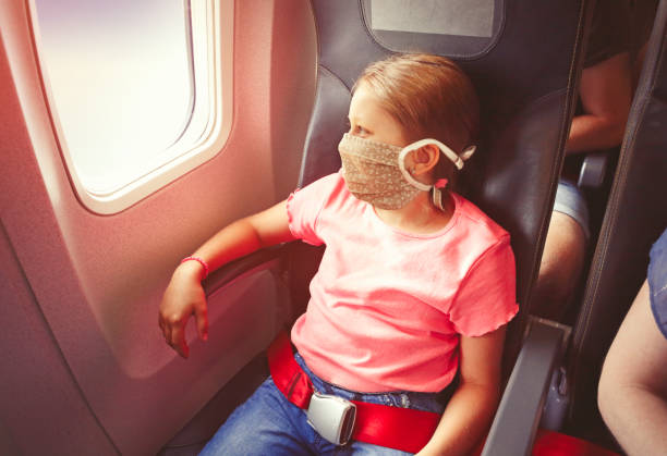 Girl with face mask flying by airplane stock photo