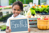 Young African American girl at farmers market with farm fresh sign.