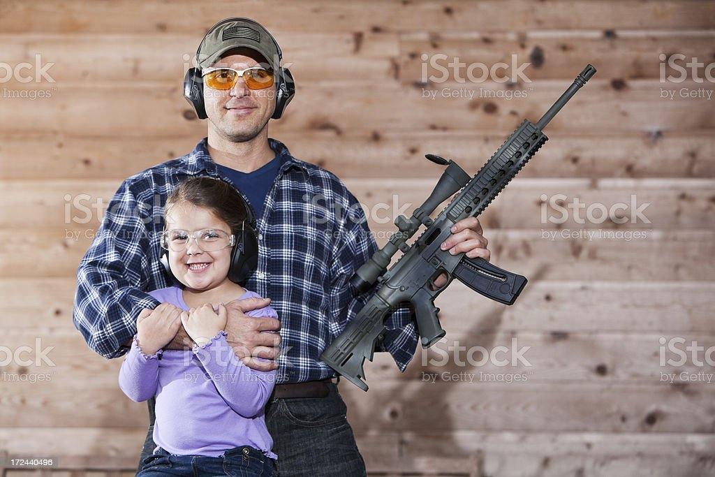 Girl with father holding rifle. stock photo