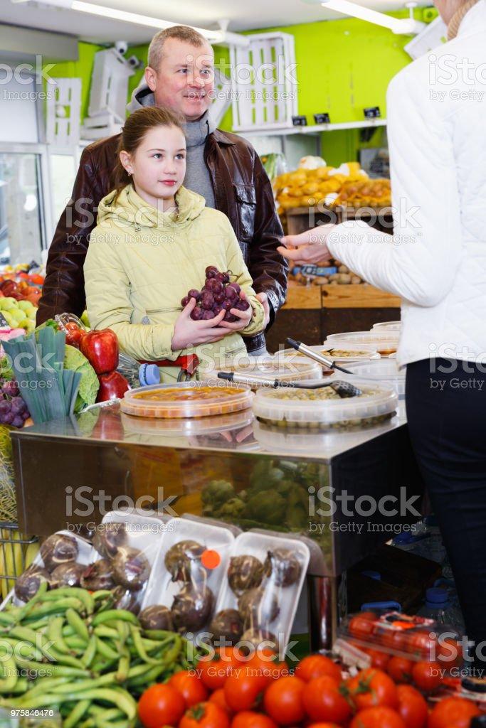 Mädchen mit Vater im Gespräch mit der Verkäuferin im Gemüsehandel - Lizenzfrei Alleinerzieher Stock-Foto
