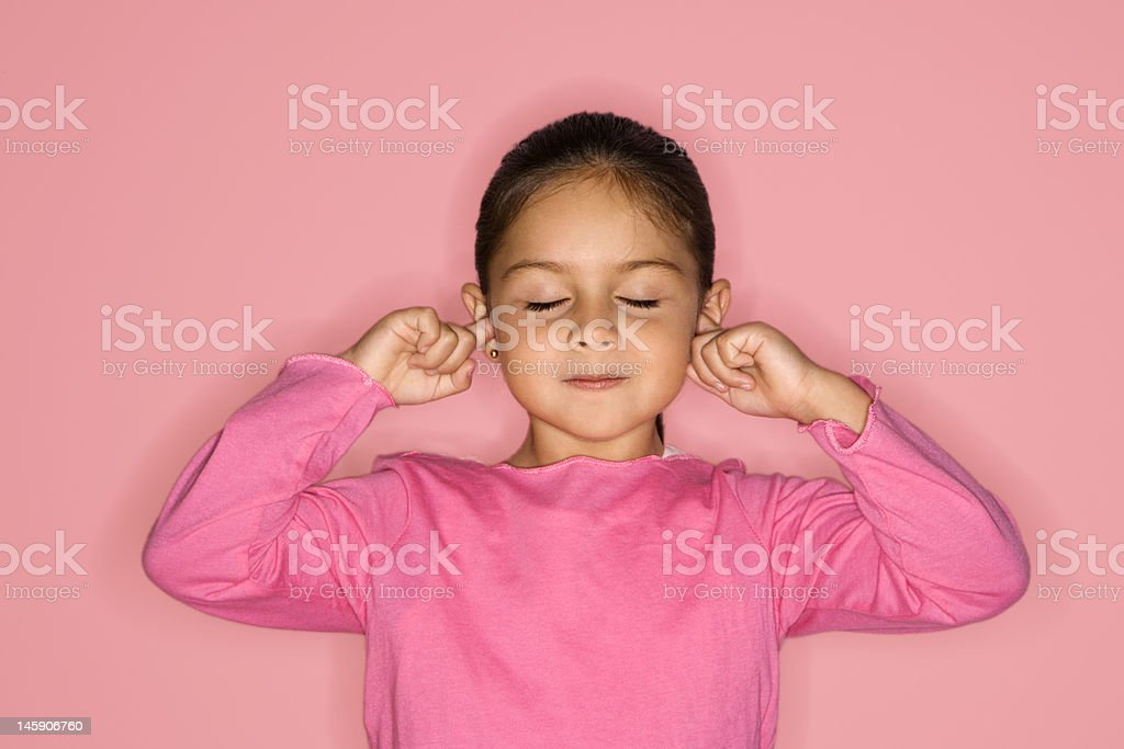 Girl with fingers in ears. stock photo