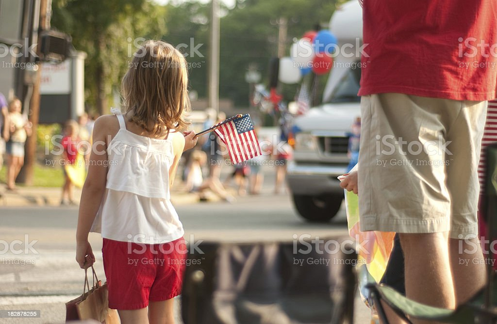 Girl with flags watches 4th of July parade in America stock photo