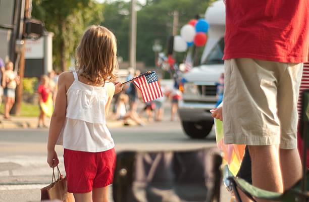 girl with flags watches 4th of july parade in america - geçit töreni stok fotoğraflar ve resimler