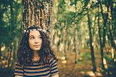森の中の自然を楽しむ花の冠を持つ少女