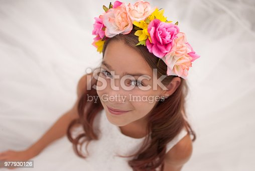 girl with brown hair and brown eyes wearing white dress and flower headband closeup looking at camera