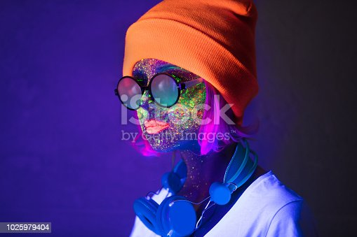 istock girl with fluorescent paint and headphones 1025979404