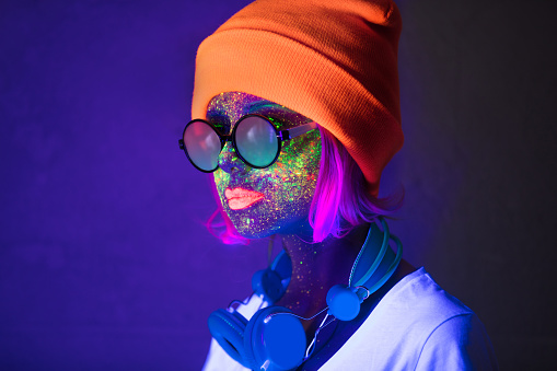 Young girl in hat with fluorescent paint on lips and face and headphones. Studio shot.