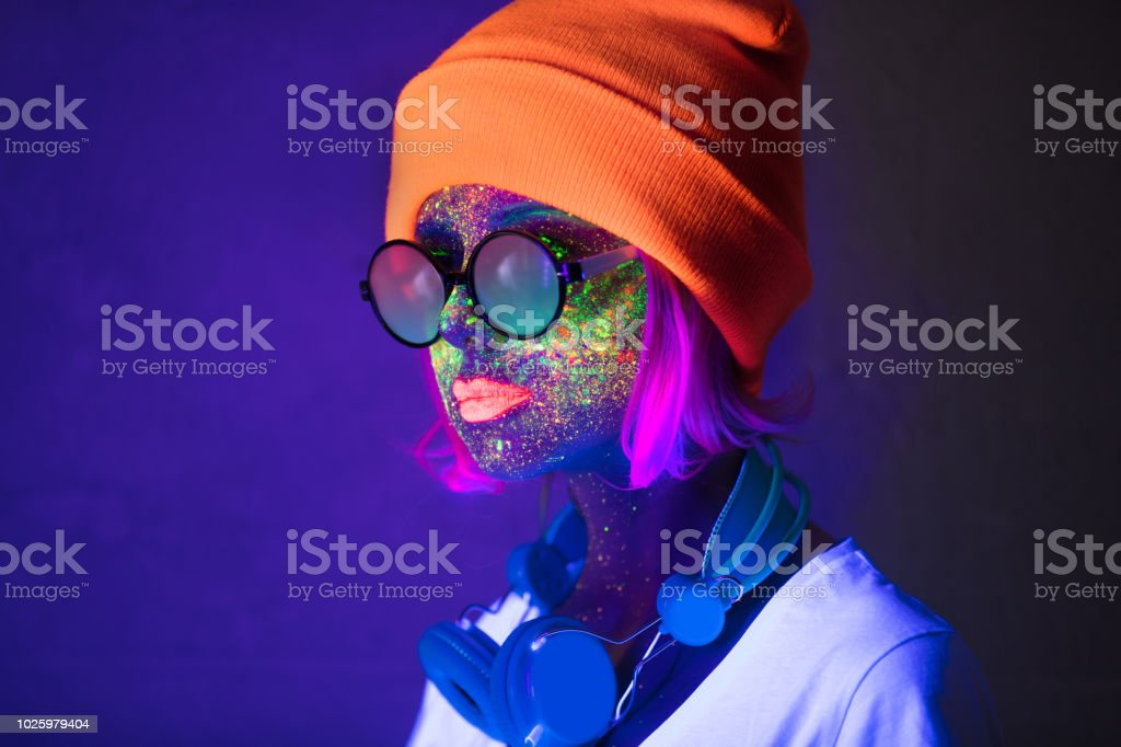 girl with fluorescent paint and headphones stock photo