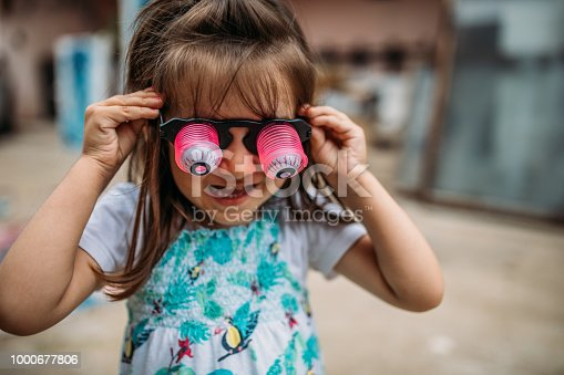Little Girl With Novelty Glasses Standing Outdoors