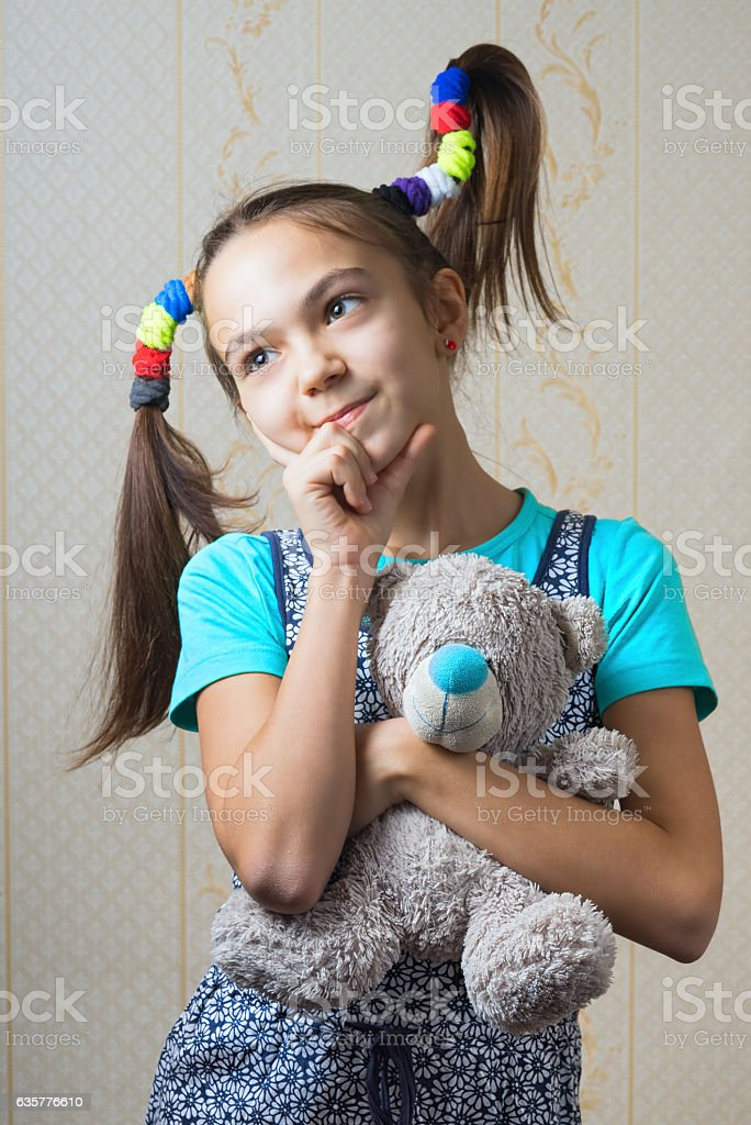girl with funny tails hugging a teddy bear stock photo