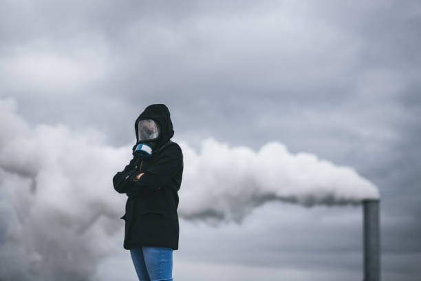 Girl with gas mask over smoking chimney. stock photo