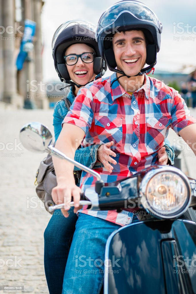 Girl with glasses sitting on pillion seat of scooter stock photo