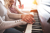 An unrecognizable teenage girl with grandmother playing the piano at home. Family and generations concept.
