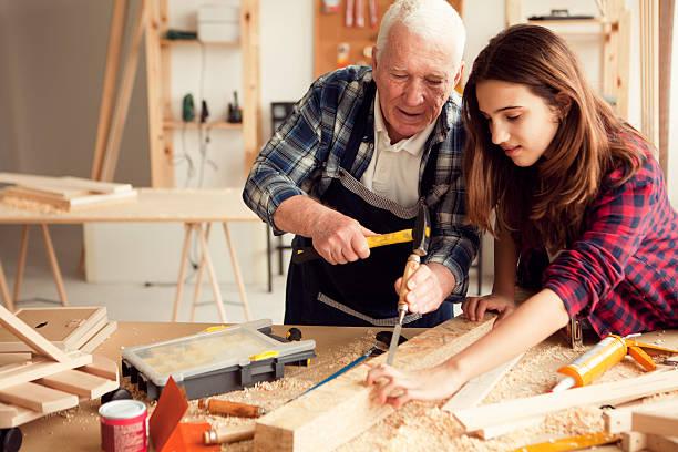 mädchen mit opa im workshop - altbau stock-fotos und bilder