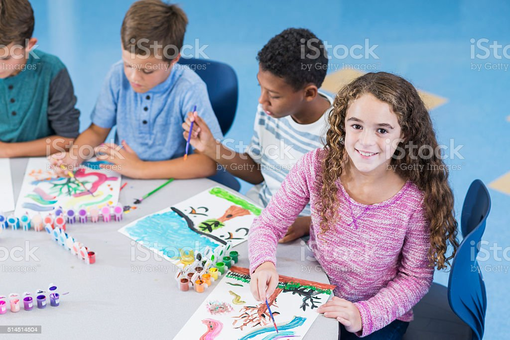 Girl with group of boys in art class smiling stock photo