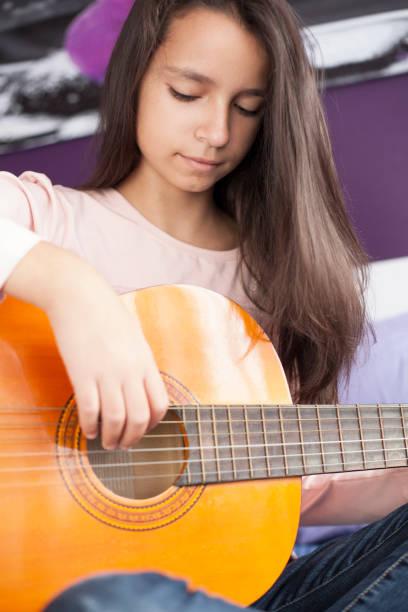 mädchen mit gitarre - lila teenschlafzimmer stock-fotos und bilder