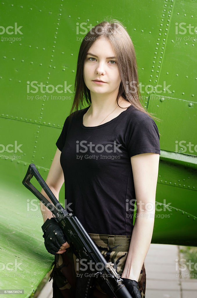 Girl with gun, posing near fuselage military transport aircraft stock photo