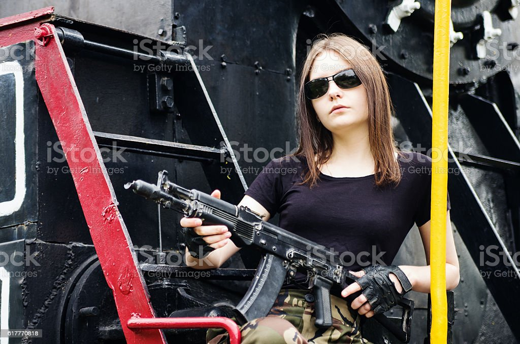 Girl with gun sitting on running board of steam locomotive stock photo