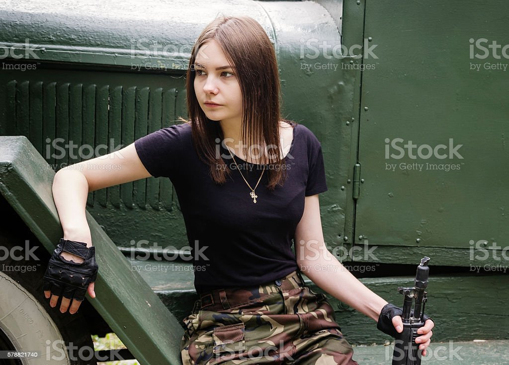 Girl with gun sitting on the steps of army truck stock photo