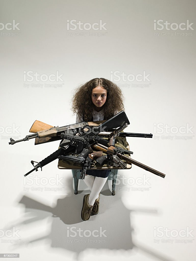 Girl with guns on desk royalty-free stock photo
