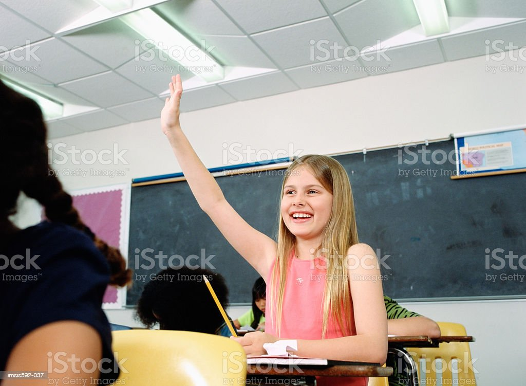 Girl with hand raised in classroom royalty free stockfoto