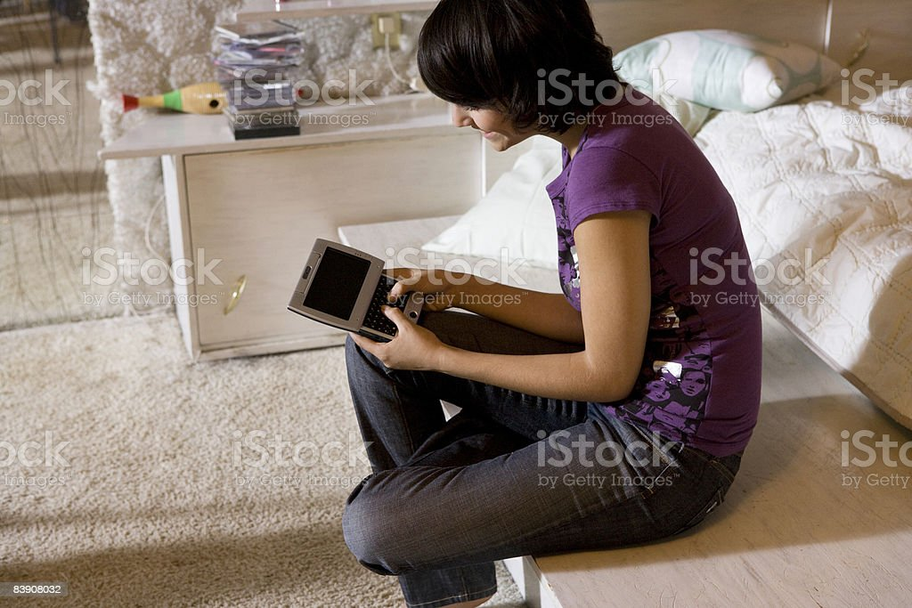 girl with handheld device sitting in white bedroom foto stock royalty-free