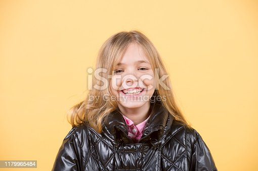 Girl with happy smile on adorable face with blond long hair on orange background.