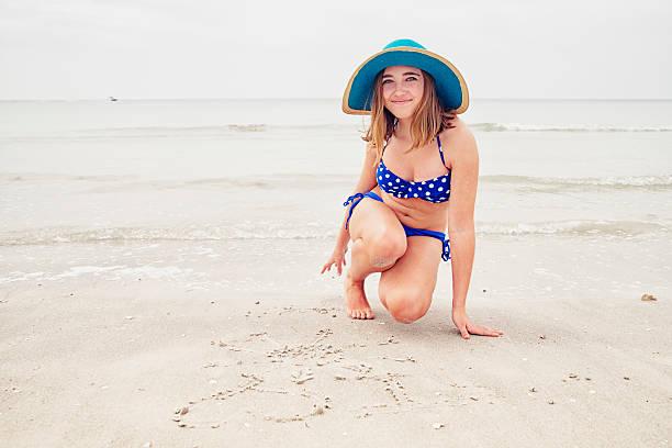 Girl with hat and bikini writing on beach. stock photo