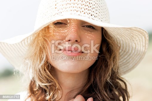 98bc95ad163 istock Girl with hat on summer sun 858531712