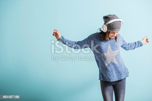istock Girl with head phones dancing and listening to music 464467186
