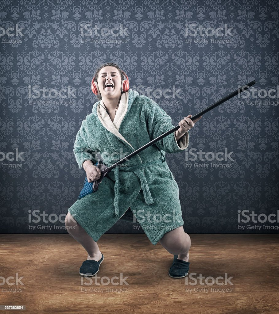 Girl with headphones and a broom stock photo