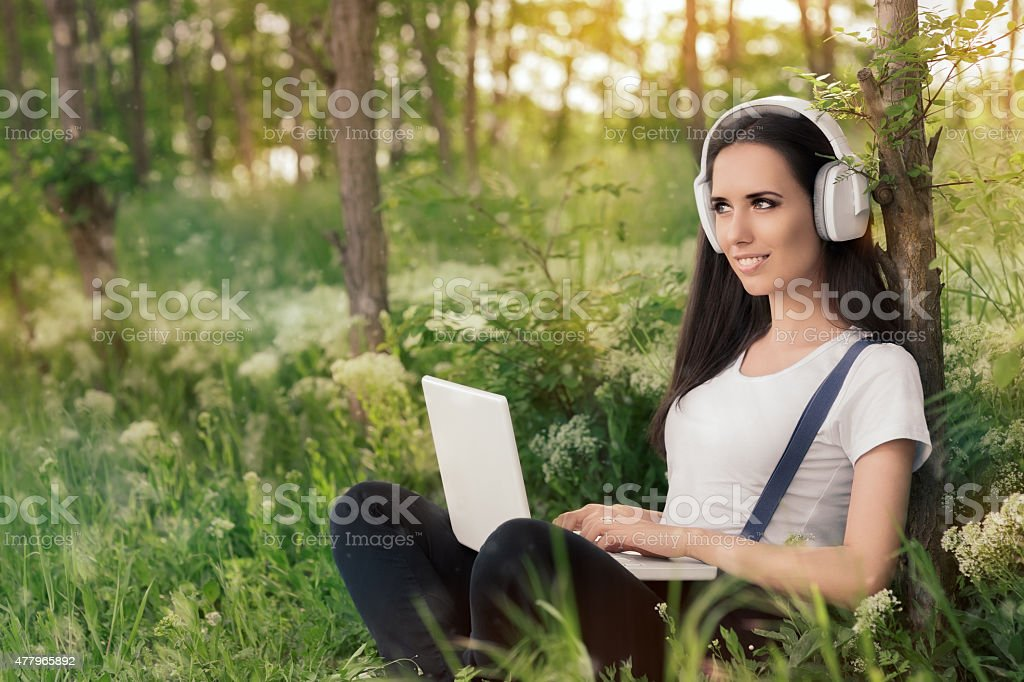 Girl with Headphones and Laptop stock photo