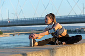 Athlete with headphones doing stretching exercises by the river