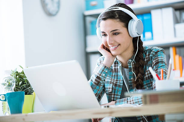girl with headphones using a laptop - video still stock pictures, royalty-free photos & images