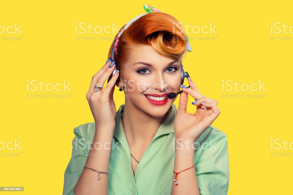 Girl with headset Closeup red head beautiful young woman pretty happy smiling pinup girl green button shirt holding microphone earphone with one hand looking at you camera retro vintage 50's hairstyle stock photo