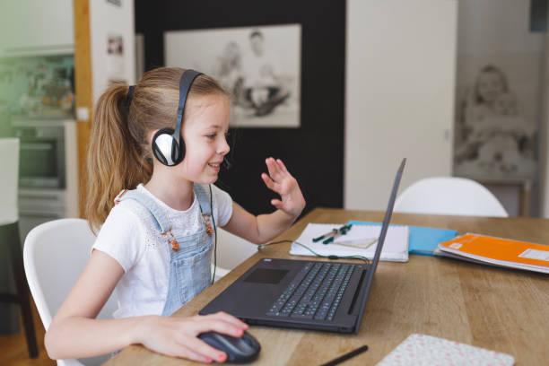 Mädchen mit Headset sitzt vor ihrem Laptop – Foto