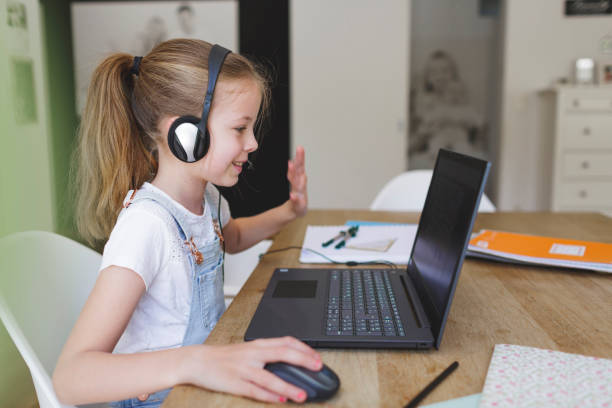 girl with headset is sitting in front of her laptop stock photo