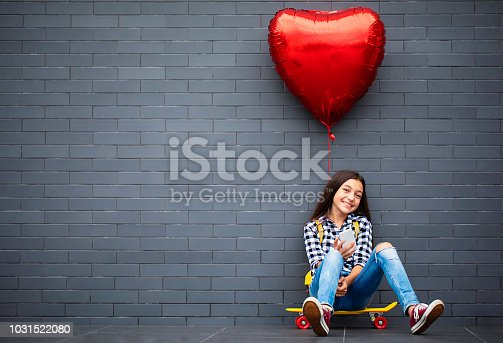 Teenage girl with heart shape air balloon, skateboard and mobile phone.