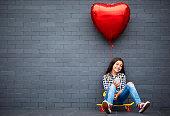 Teenage girl with heart shape air balloon, skateboard and mobile phone.