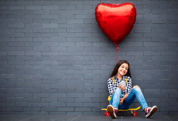 Girl with heart shape air balloon Teenage girl with heart shape air balloon, skateboard and mobile phone. digital native stock pictures, royalty-free photos & images