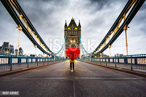 istock Girl with heart shaped umbrella on Tower Bridge, London 909149582