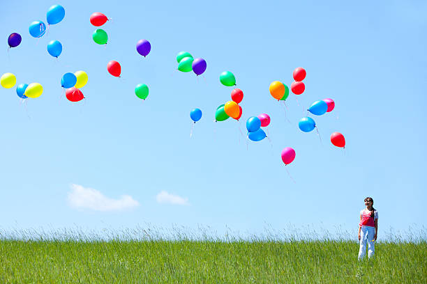 Girl with helium balloons stock photo