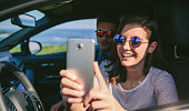 Girl with her boyfriend taking a selfie with the cell phone in the car. Selective focus on girl in background