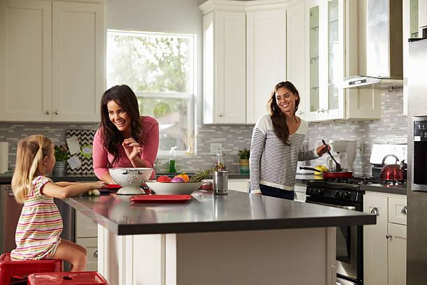 weibliche mädchen mit ihren eltern, die zubereitung von essen in der küche - küche aus paletten stock-fotos und bilder