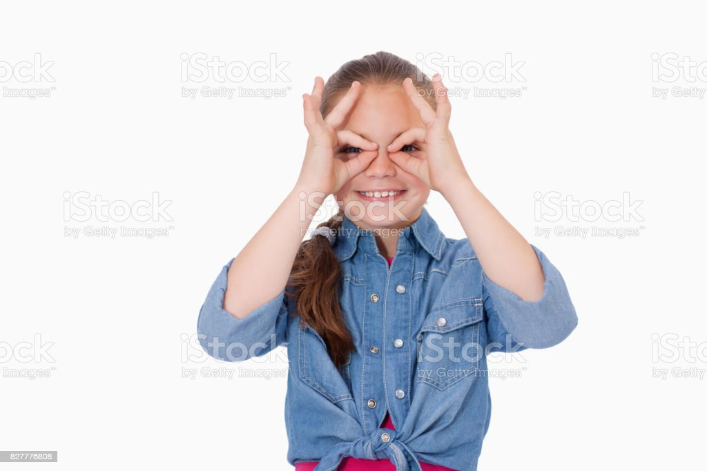 Girl with her fingers around her eyes stock photo