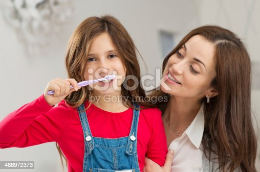 800444456 istock photo Girl With Her Mother Brushing Teeth 466972373