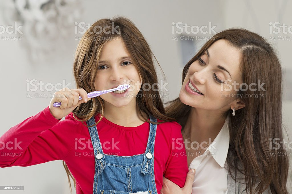 Girl With Her Mother Brushing Teeth stock photo