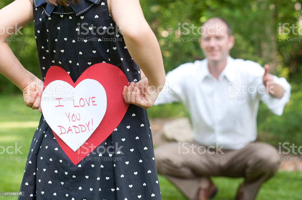 Girl with I love you daddy card for her father royalty-free stock photo
