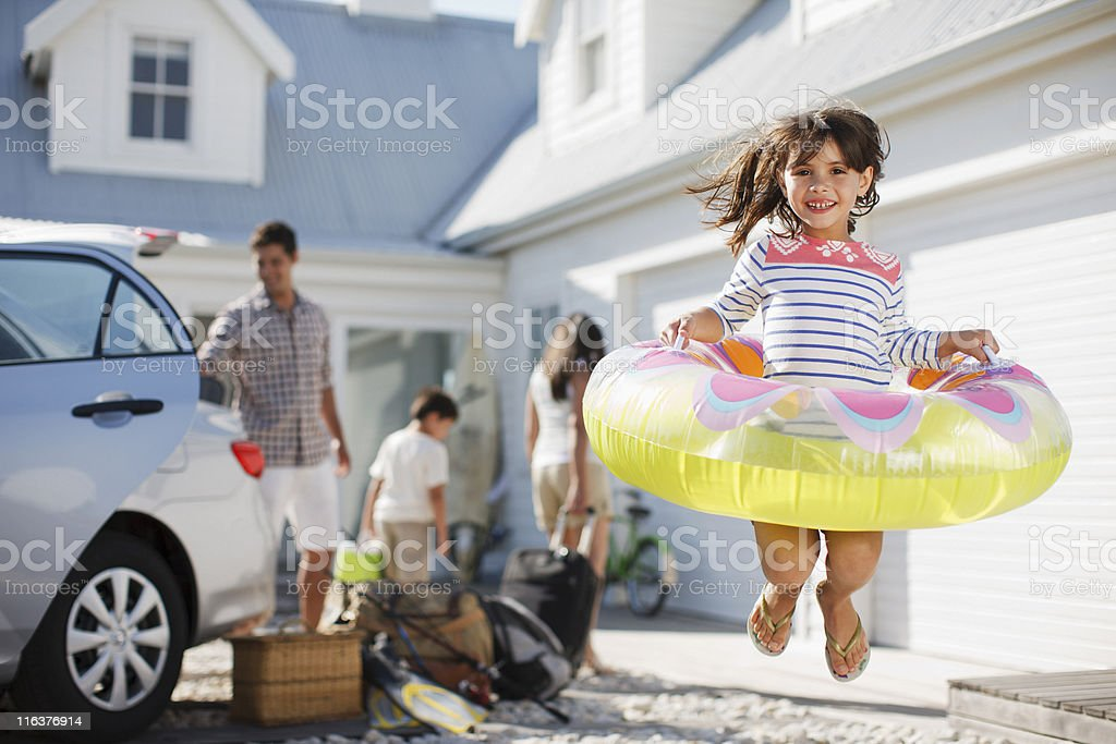 Girl with inflatable ring jumping in driveway stock photo