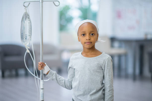Girl With IV A young girl of African descent is indoors in a hospital room. She has cancer, and she is wearing a hat. She is looking at the camera while hooked up to an IV. cancer cell stock pictures, royalty-free photos & images